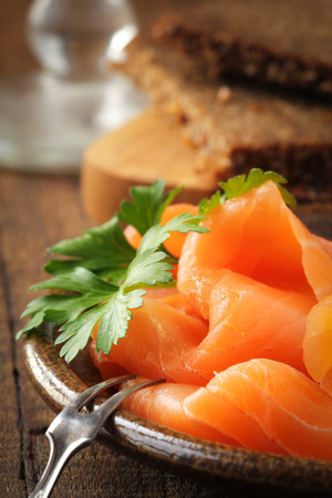 Slices of smoked salmon with a fresh leaf of parsley on a dark rustic plate with rye bread at the background photo