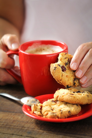 christmas morning: Female hands holding a cup of hot frothy cappuccino in a red mug and a crispy cranberry cookie for a Christmas morning Stock Photo