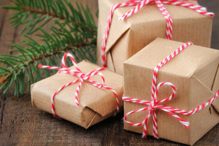 Three handcrafted Christmas gifts wrapped in brown paper and tied with a red and white festive twine