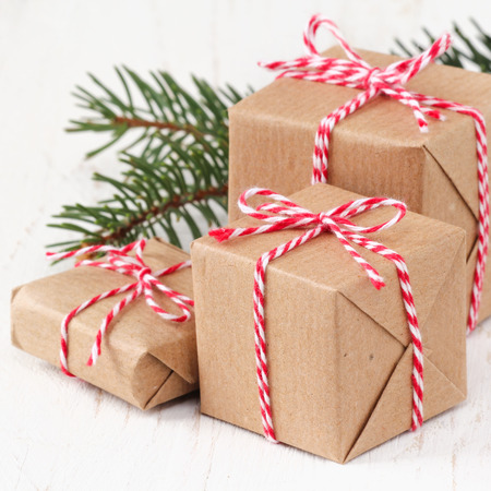christmas baker's: Group of three Christmas presents wrapped in brown paper and ties with a festive red and and white bakers twine on white wooden background