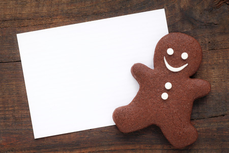 White Chrisyìtmas greeting card on rustic wooden surface with a traditional smiling gingerbread man cookie 版權商用圖片