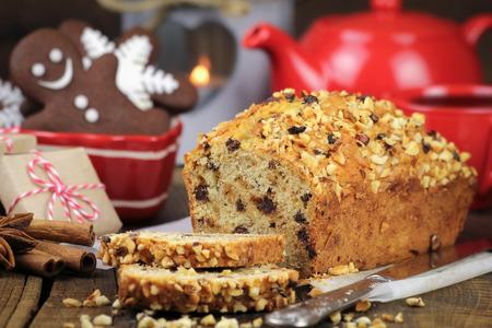 cioccolato natale: Accogliente Natale tabella con una torta di festa appena sfornata affettato con cioccolato e noci tritate, teiera rossa, biscotti di panpepato, regali e una lanterna con una candela accesa sullo sfondo