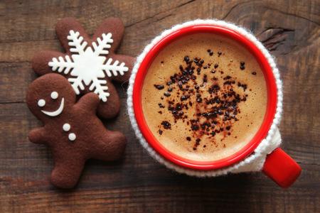 Guten Morgen und einen schönen Tag Frohe Weihnachten Nachricht Konzept - leuchtend roten Tasse Kaffee von schaumig mit einem weißen gestrickten Becherhalter und traditionell eingerichtete festliche Schneeflocke und Lebkuchenmann Schokolade Cookies fallen