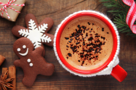 Good morning Christmas concept - red cup of coffee with decorated xmas snowflake and gingerbread cookies surrounded with festive decoration and gifts photo