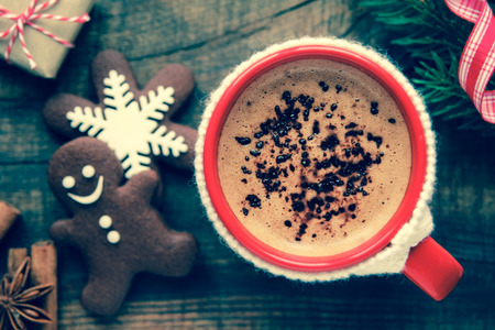 Good morning Christmas concept - red cup of coffee with decorated xmas snowflake and gingerbread cookies surrounded with festive decoration and gifts. With retro vintage filter effect photo