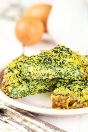 Homemade Italian spinach or Swiss chard frittata - baked spinach omelet with ingredients at the background photo