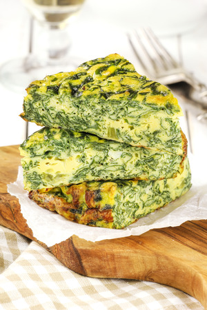 Stack od sliced Italian spinach frittata or omelet on a rustic wooden cutting board photo