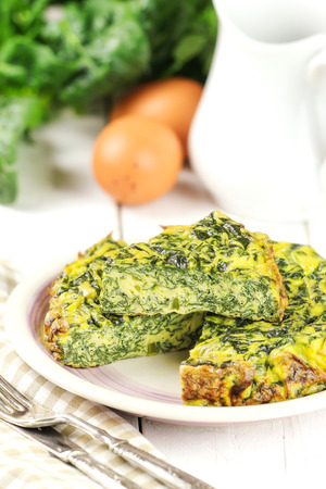 omelet: Homemade Italian spinach or Swiss chard frittata - baked spinach omelet with ingredients at the background