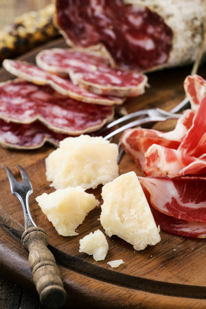 Traditional Italian appetizer - parmesan cheese, cold cut prosciutto ham and cured salami on a rustic wooden cutting board