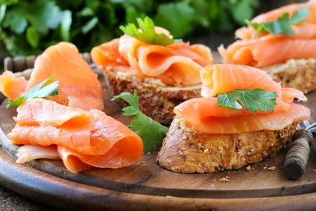 salmon ahumado: Deliciosa casera canapé fumado libre de gluten salmón adornado con una hoja de perejil fresco en la madera