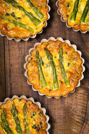 tart: Delicious freshly baked homemade spinach and asparagus frittata or omelette in tart moulds on rustic wooden table. Overhead view Stock Photo