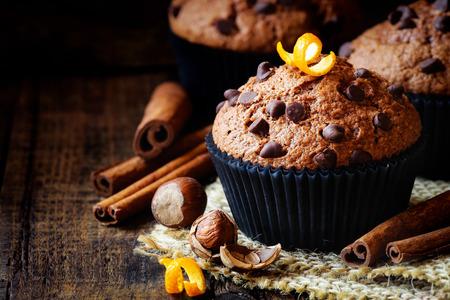 avellanas: Hecho en casa de chispas de chocolate de naranja y panecillos de canela en backgroung rústico oscuro Foto de archivo