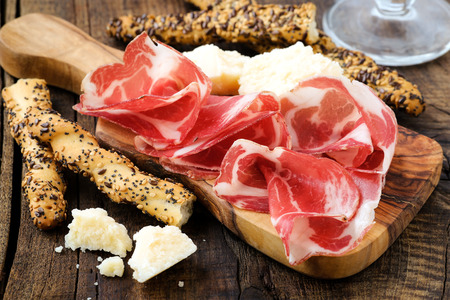 Traditional Italian appetizer - cured prosciutto ham or coppa on a wooden serving board with breadsticks and parmesan cheese