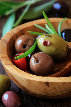pitted: Assorted pitted olives with rosemary in wooden bowl Archivio Fotografico