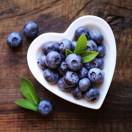 healthy snack: Fresh ripe garden blueberries in a white heart shape bowl on dark rustic wooden table. with copy space for your text