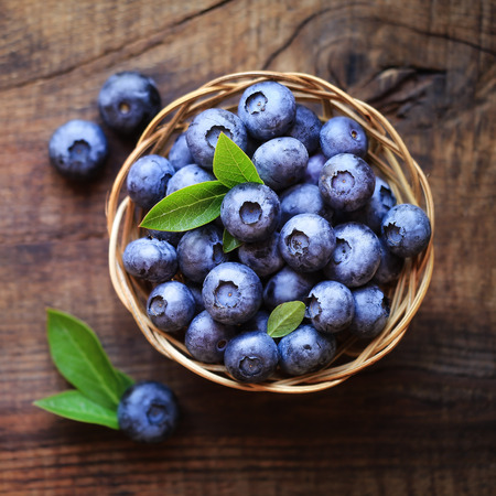 Fresh ripe garden blueberries in a wicker bowl on dark rustic wooden table. with copy space for your text 版權商用圖片