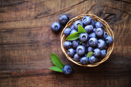 fruit bowl: Fresh ripe garden blueberries in a wicker bowl on dark rustic wooden table. with copy space for your text Stock Photo
