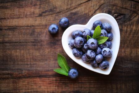 어두운 소박한 나무 테이블에 흰색 심장 모양의 그릇에 잘 익은 신선한 정원 블루 베리입니다. 텍스트 복사 공간 스톡 콘텐츠