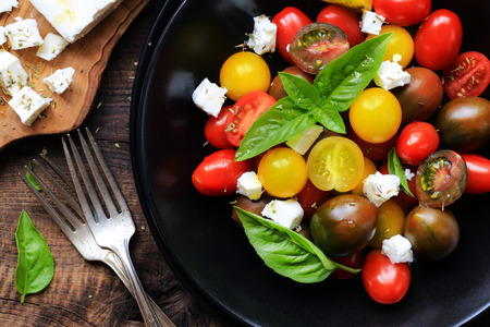 Healthy light summer salad with colourful cherry tomatoes and feta cheese decorated with fresh basil