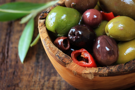 pitted: Closeup of assortment of pitted olives in brine in a rustic wooden bowl