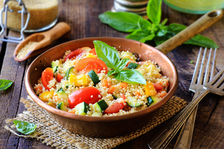 carrot: Delicious homemade vegetarian couscous with tomatoes, carrots, zucchini, yellow bell pepper and fresh basil on a dark rustic wooden kitchen table