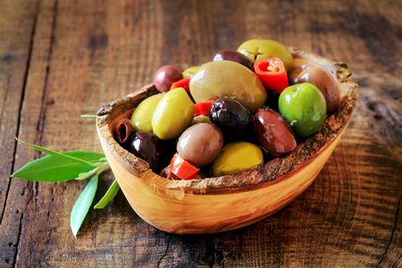 brine: Assortment of pitted olives in brine in a rustic wooden bowl