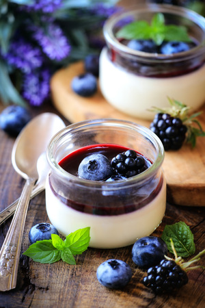 panna cotta: Panna cotta with blueberry and blackberry coulis - Traditional homemade Italian dessert served in glass jars and decorated with fresh berries and a sprig of mint on dark rustic wooden background