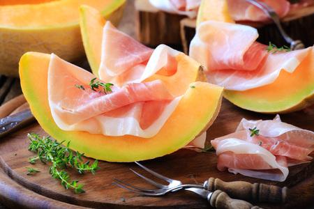 jamon: Prosciutto italiano con melón con tomillo fresco en la mesa de cocina de madera rústica