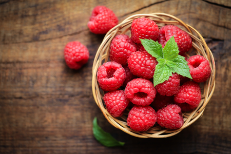 summer fruits: Fresh ripe red raspberries in a wicjer bowl on dark rustic wooden background Stock Photo