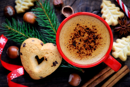 cintas navide�as: Buenos d�as o tener un concepto agradable d�a Feliz Navidad mensaje - Taza de caf� con forma de coraz�n festivo y galletas de la forma del �rbol de Navidad, abeto fresca o rama de pino, las avellanas, los palitos de canela y una cinta decorativa Foto de archivo