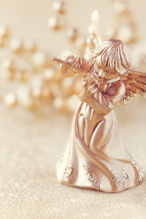 angel figurine: Christmas angel playing a flute with golden decoration at the background Stock Photo