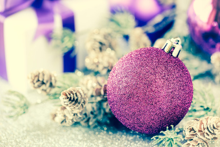 Purple Christmas bauble with pine or fir branch and a wrapped gift with purple ribbon on silver background