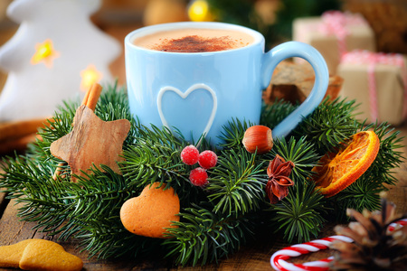 christmas morning: Good morning concept - cup of frothy coffee and a decorated Christmas wreath with gifts and candles at the background