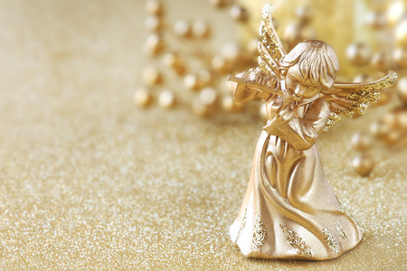 angel: Christmas angel playing a flute with golden decoration at the background Stock Photo