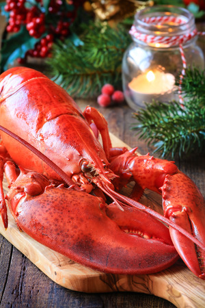 christmas dish: Delicious cooked lobster on wooden cutting board as a concept of Christmas cooking with a candle and fir or pine branches at the  background