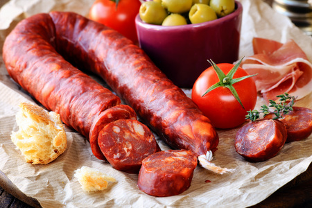 Sliced Spanish chorizo sausage with bread, olives, jamon serrano and tomatoes