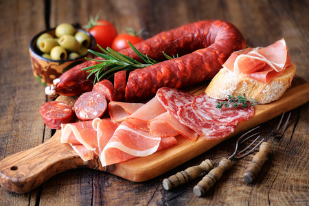 frankfurter: Cured meat platter of traditional Spanish tapas - chorizo, salsichon, jamon serrano, lomo - erved on wooden board with olives and bread Stock Photo
