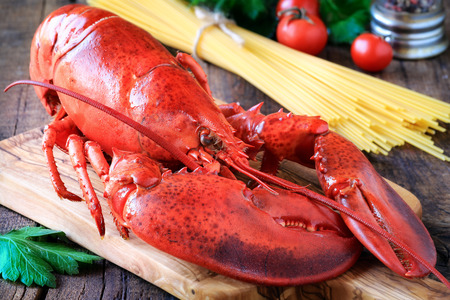 Delicious steamed lobster on wooden cutting board and spaghetti at the background