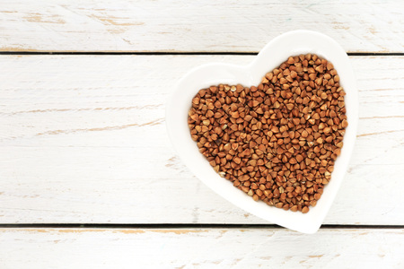 desease: Buckwheat groats in a heart shaped bowl on white wooden background with copyspace for your text