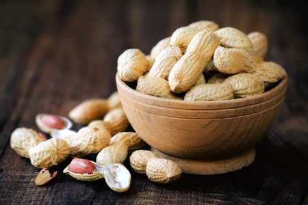 Peanuts in a bowl on dark rustic wooden background. Shallow DOF with copy space for your text 版權商用圖片