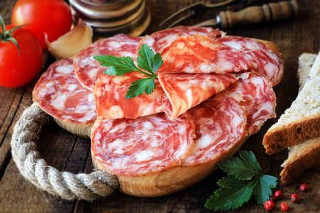 salame: Spanish tapas - sliced salame on rustic wooden cutting board with bread and tomatoes