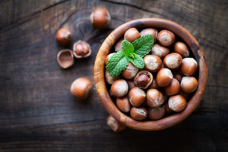 cobnut: Shelled hazelnuts in a wooden bowl against dark rustic wooden background. Overhead view with shallow depth of field