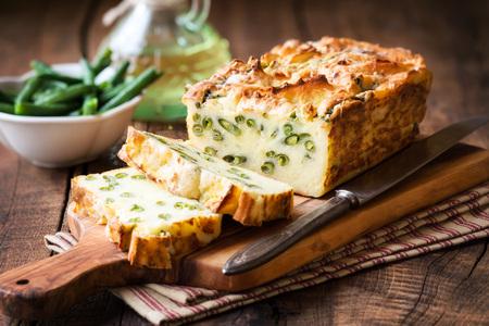 ejotes: Pan hecho en casa rústica de patata con judías verdes en rodajas en tabla para cortar madera