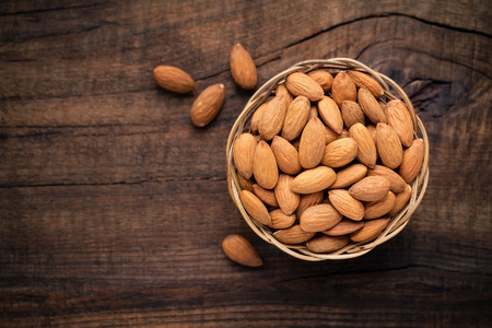 allergic ingredients: Almonds in willow bowl against dark rustic wooden background. Overhead view Stock Photo