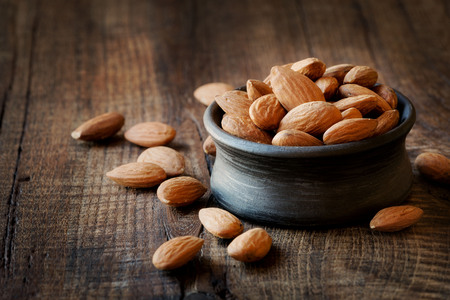 allergic ingredients: Almonds in a black bowl against dark rustic wooden background