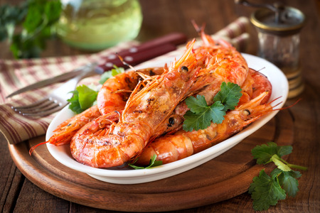 griller: Griller King prawns or shrimps with parsley on white plate on dark rustic wooden table Stock Photo