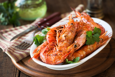 allergic ingredients: Griller King prawns or shrimps with parsley on white plate on dark rustic wooden table Stock Photo