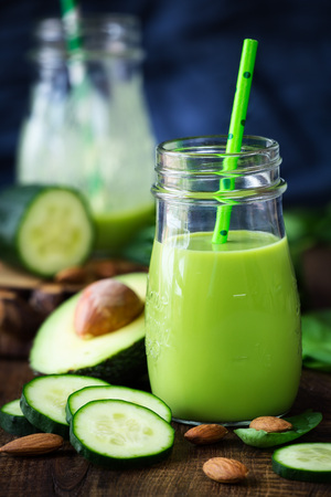 Healthy food concept - green detox smoothie with avocado, cucumber, spinach and almonds in glass jar with a straw