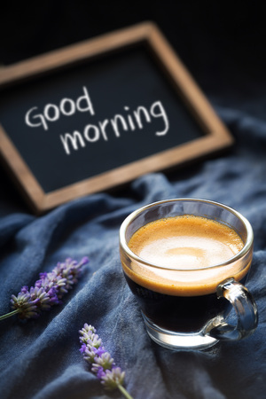 Cup of espresso against dark background with flowers or lavender and blackboard with Good Morning greeting