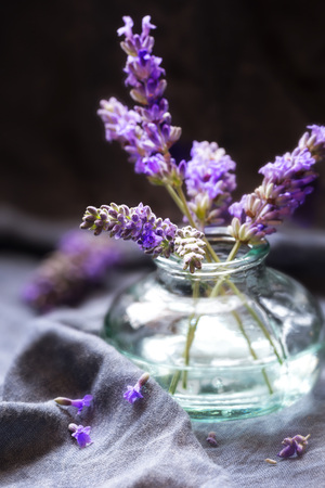 Small bunch of lavender flowers in a glass vase against dark background. Shallow depth of field